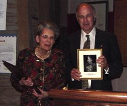 Barbara Mueller looks on as Chairman Roger Brody holds the photograph to be placed on the USSS Hall of Fame wall at the American Philatelic Center.